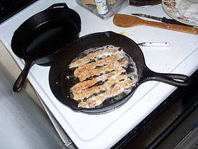 Bacon coooking in a cast iron skillet.