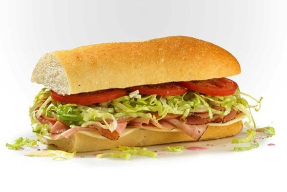 A sub sandwich with meat, shredded lettuce and tomatoes.